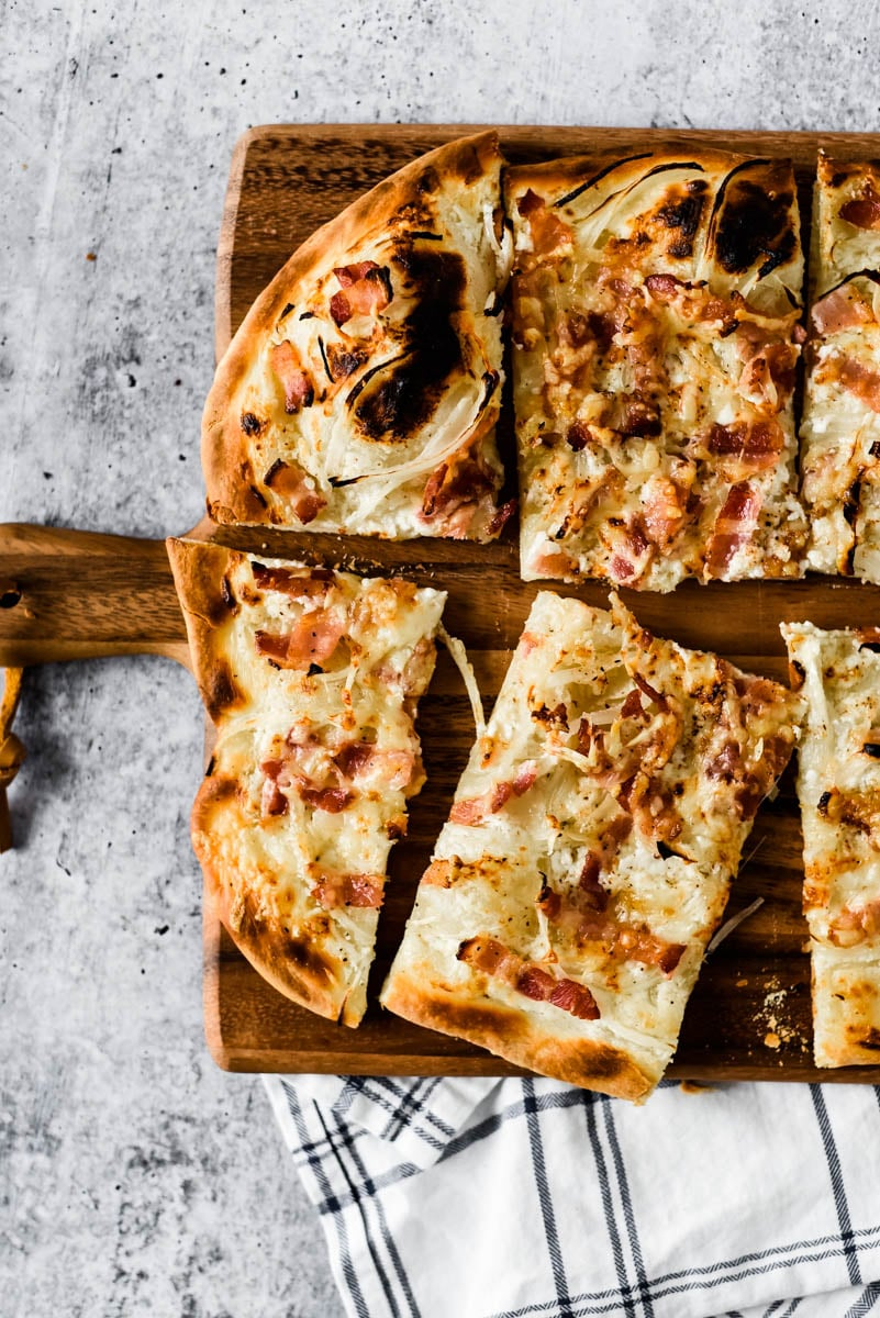 cut wedges of french bacon and onion tart on wooden cutting board