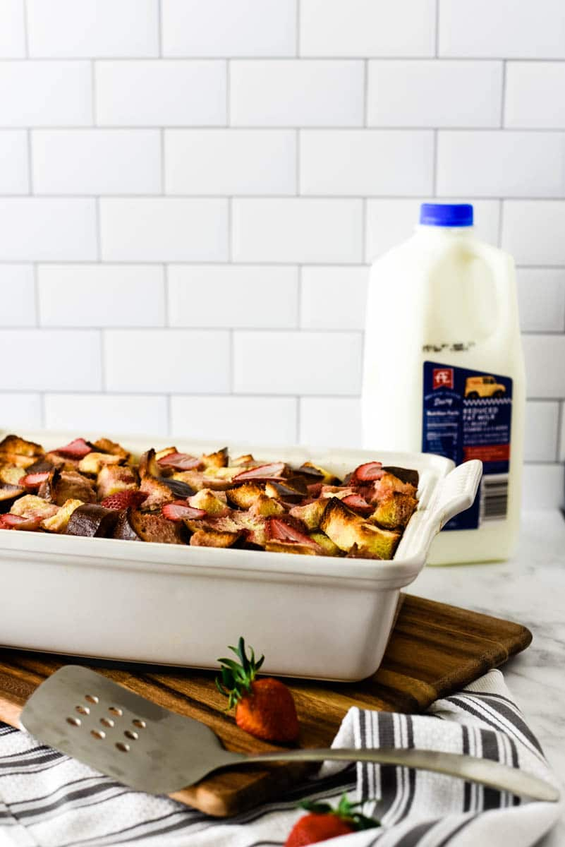 strawberry bread pudding in white stoneware dish with a half gallon of AE 2% milk behind it