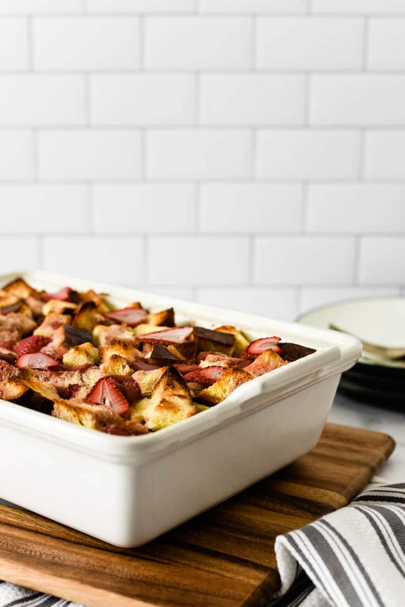 white stoneware baking dish with strawberry bread pudding