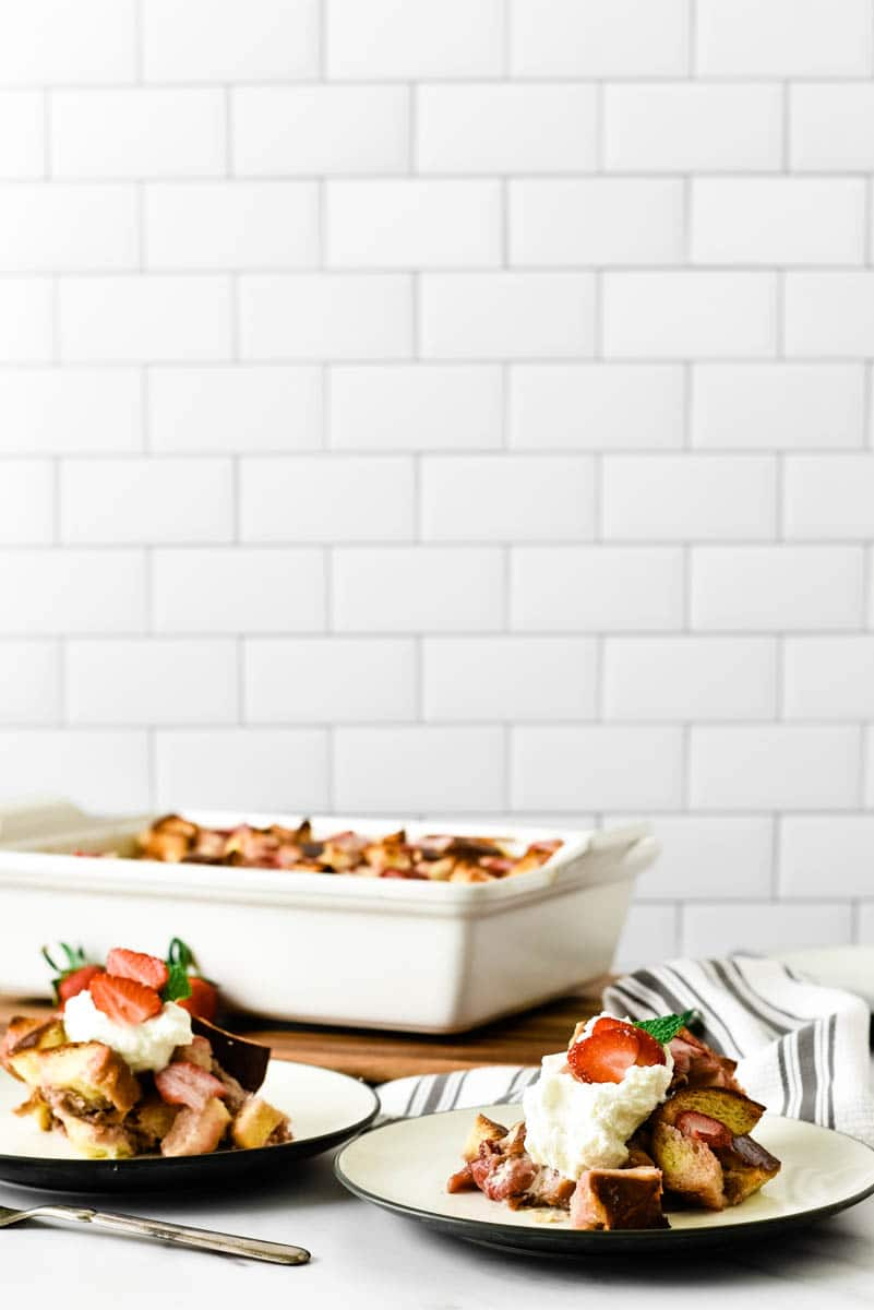 white casserole dish with two plates of bread pudding in front of it