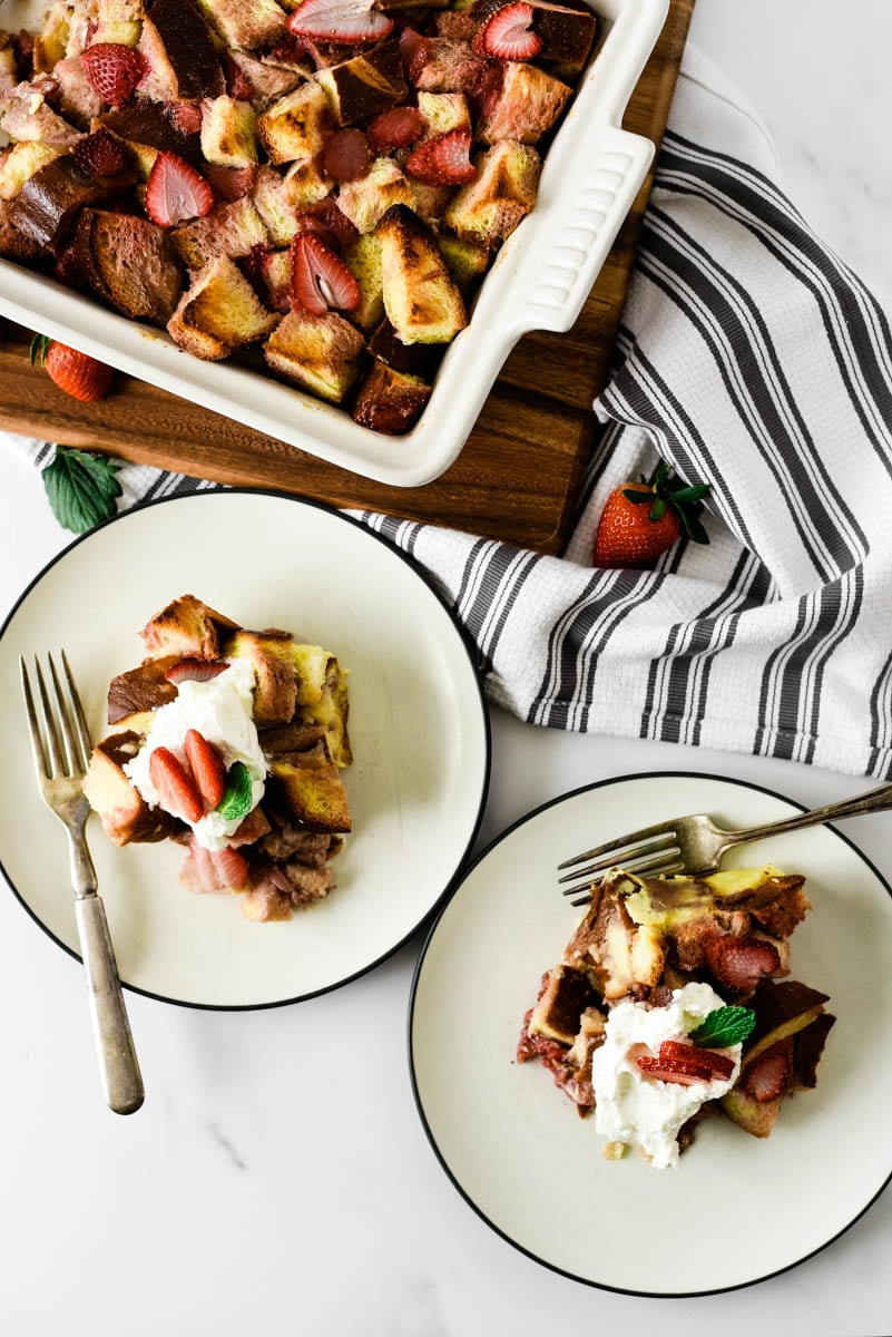 two plates with strawberry bread pudding sitting beside stoneware baking dish filled with more
