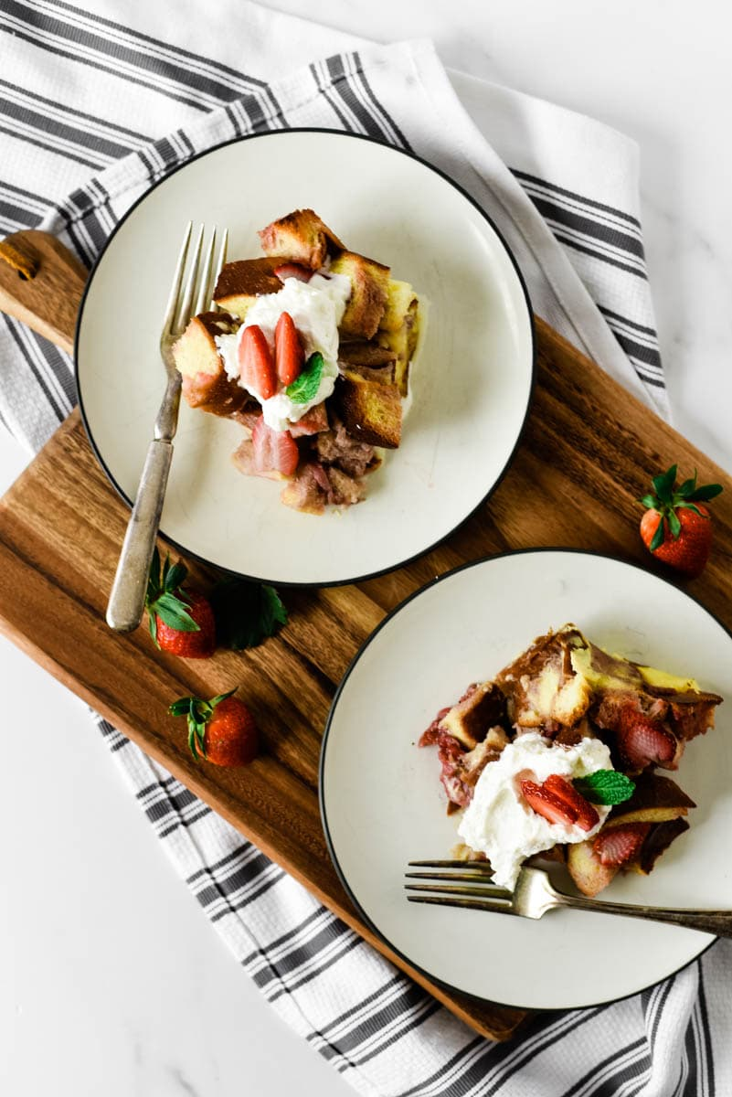 two white plates with strawberry bread pudding, with forks, on wooden cutting board surrounded by strawberries