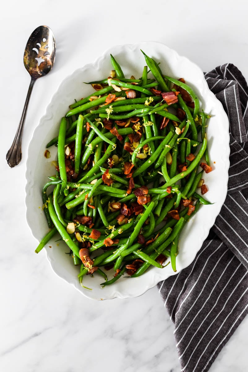 green beans almondine in white platter next to napkin and serving spoon