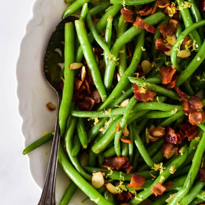 close up of green beans with bacon in white platter