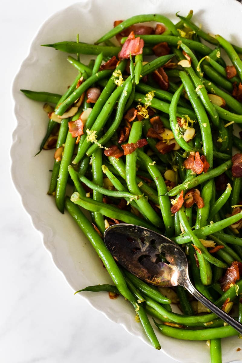 overhead image of green beans with bacon and lemon in platter