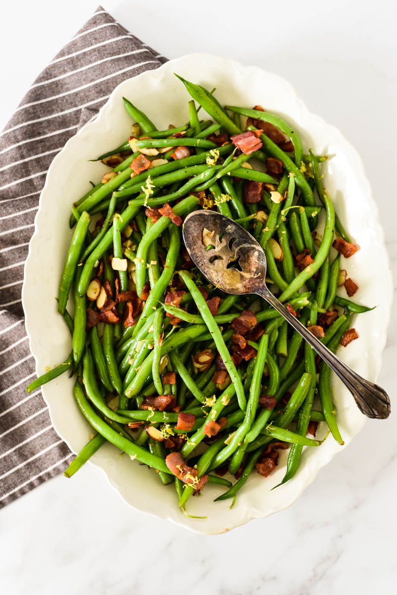 overhead view of green bean almondine in white platter with serving spoon and napkin beside