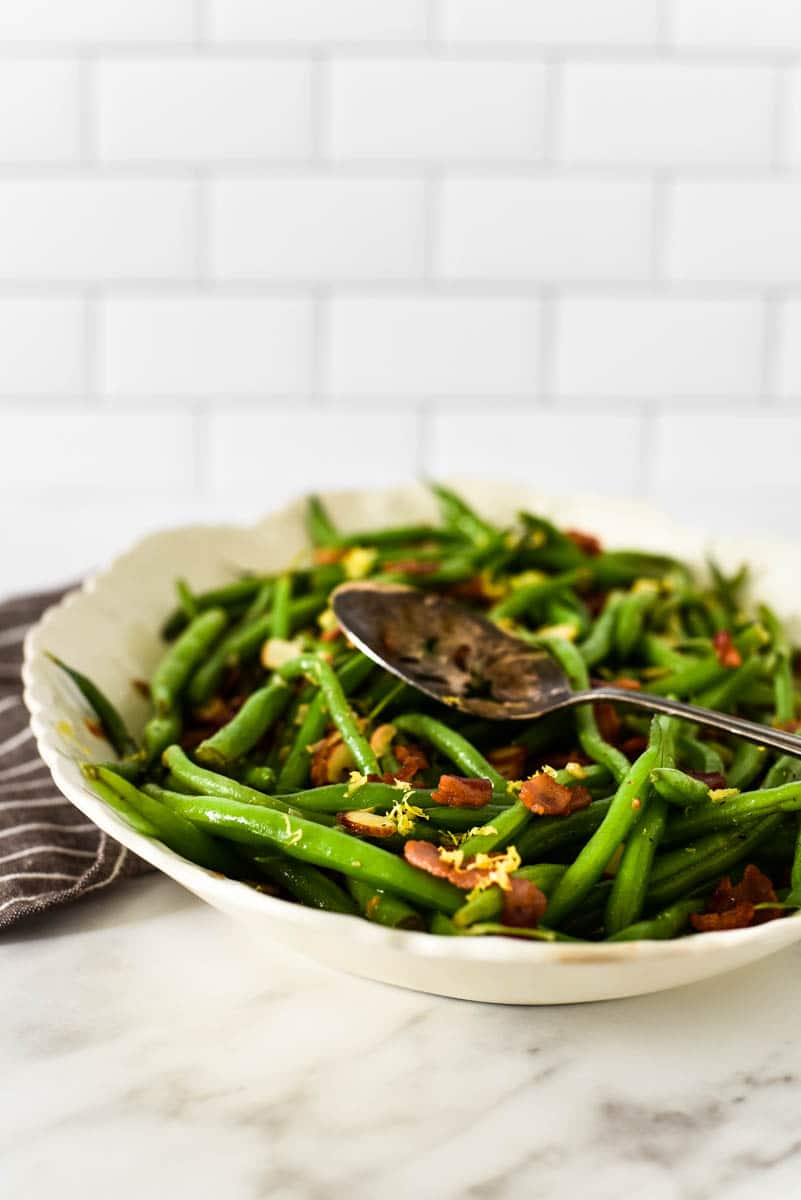 side view of green beans in white platter, topped with bacon and lemon zest