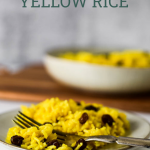 Yellow rice on plate with fork, serving dish in the background. Text overlay of recipe title for Pinterest