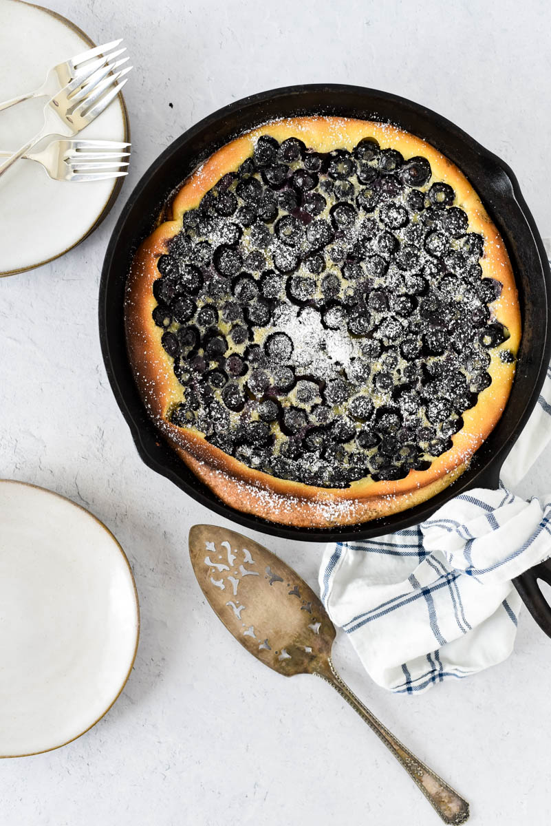 overhead view of blueberry clafoutis with napkin and serving utensils