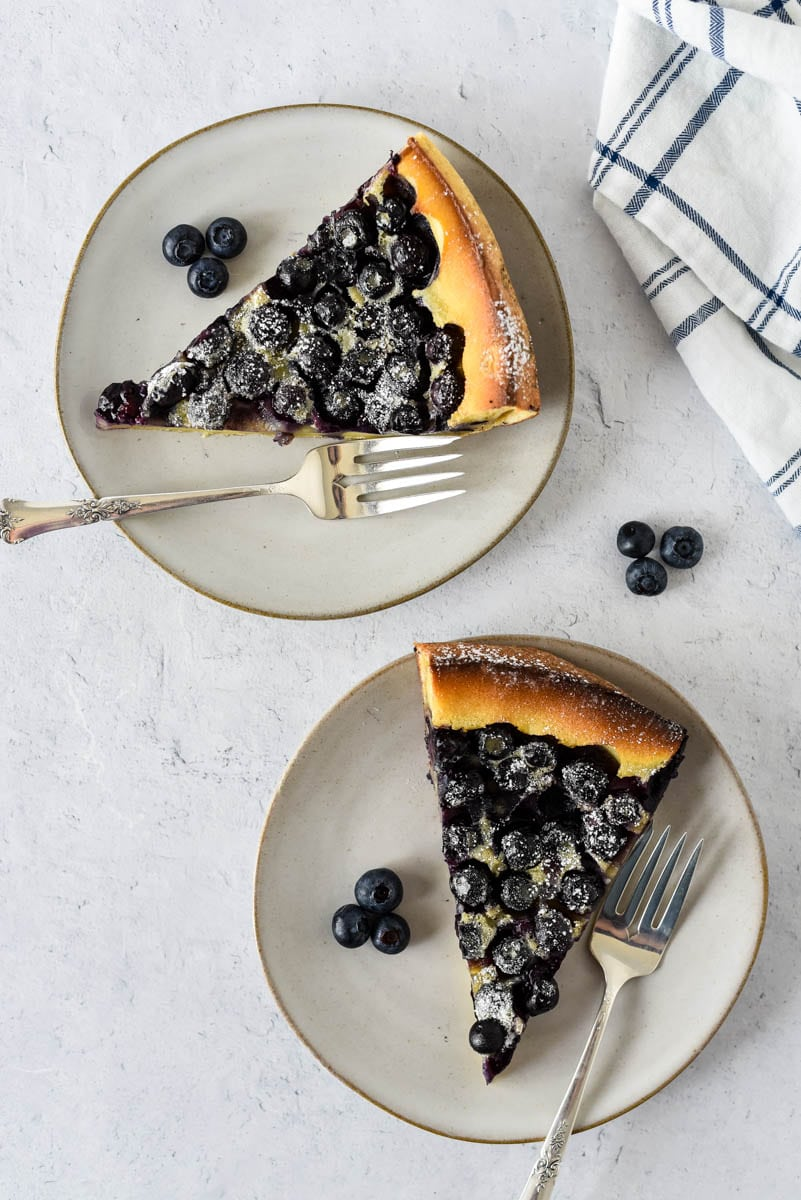 overhead view of two plates with slices of blueberry clafoutis and forks