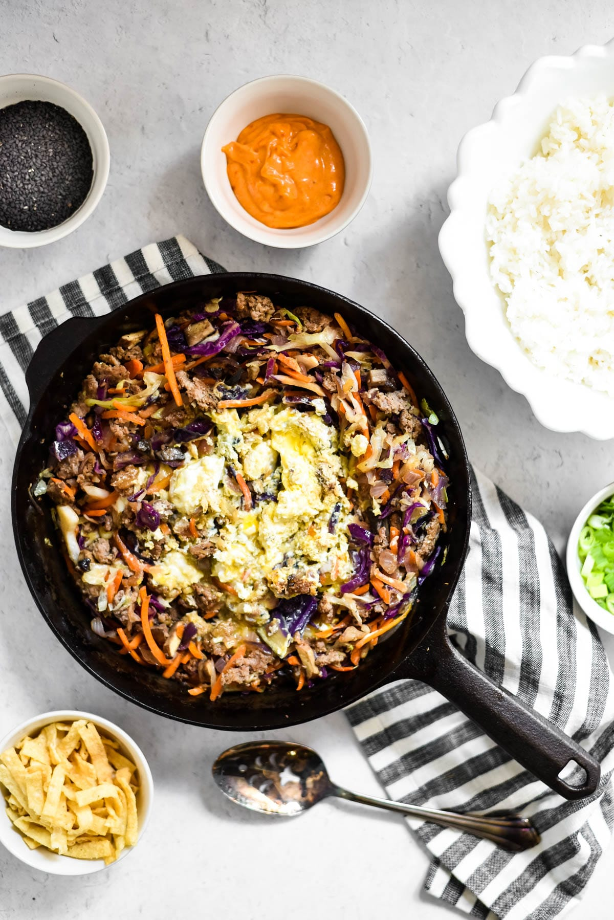 skillet with egg roll in a bowl surrounded by bowls with toppings