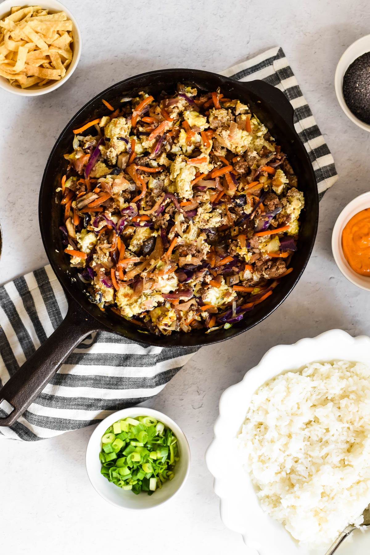 skillet with deconstructed egg roll surrounded by bowls with toppings and rice