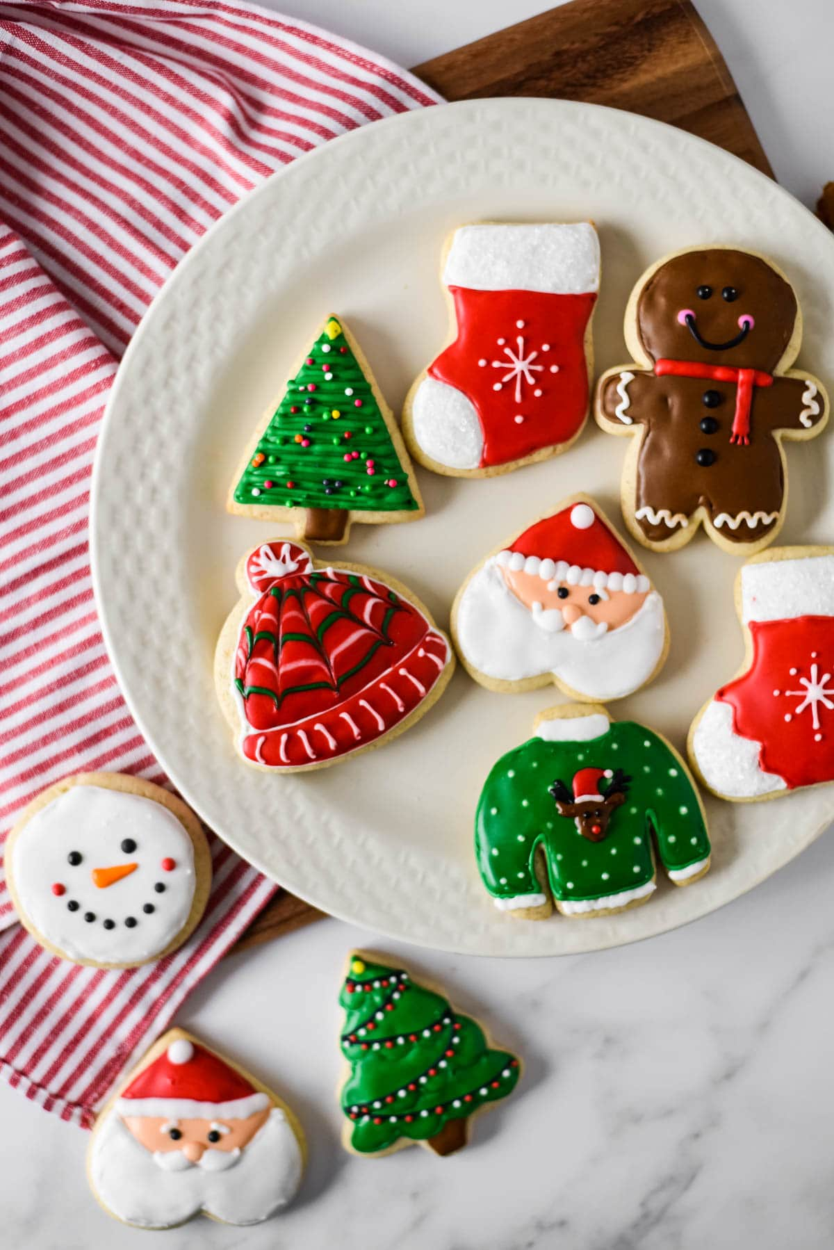 sourdough cut out cookies decorated for Christmas on a white plate beside red white striped towel