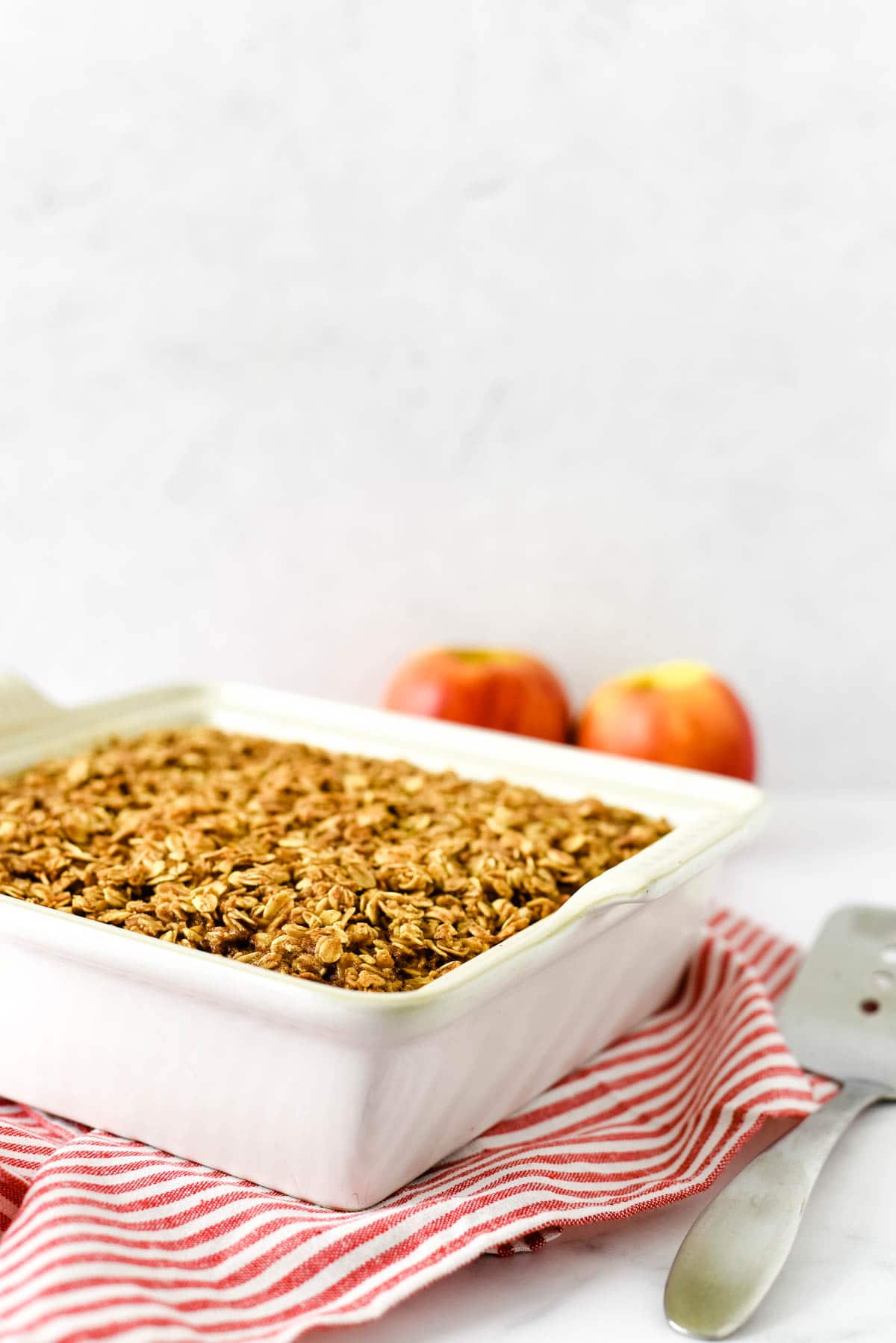 white square baking dish with baked oatmeal and two apples behind