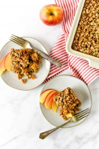 apple baked oatmeal on serving plates with dish behind