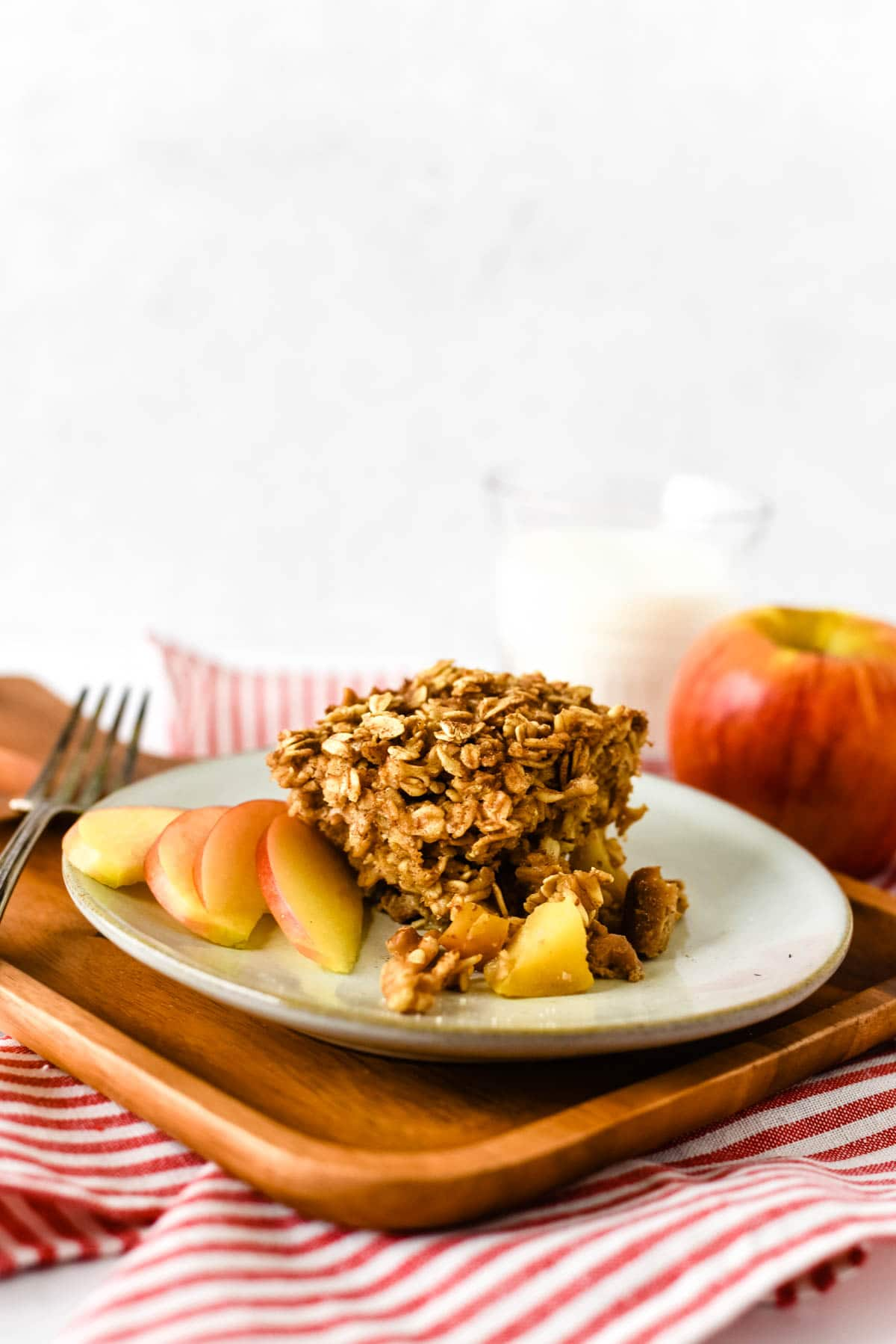 baked oatmeal with apples on plate with apple slices and glass of milk