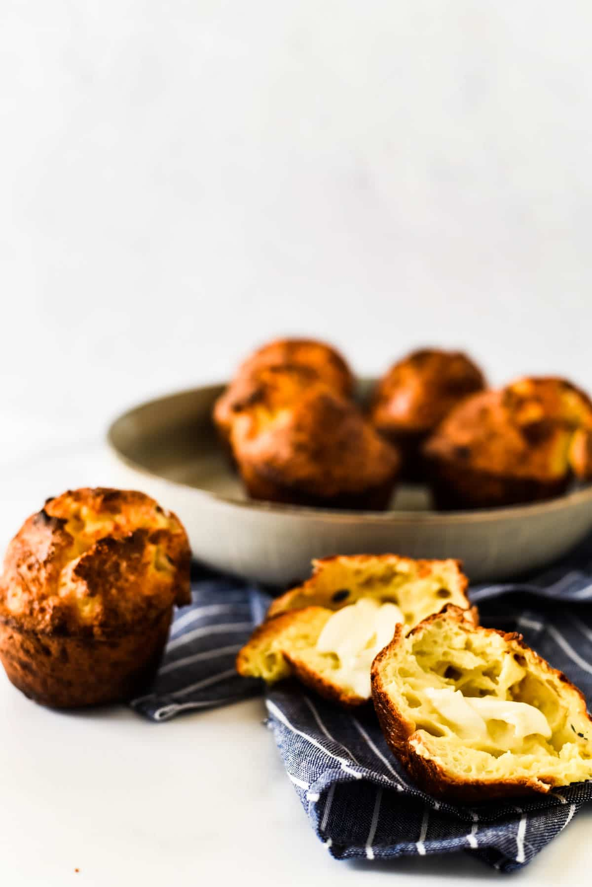 cheese popovers in bowl with one split open with butter