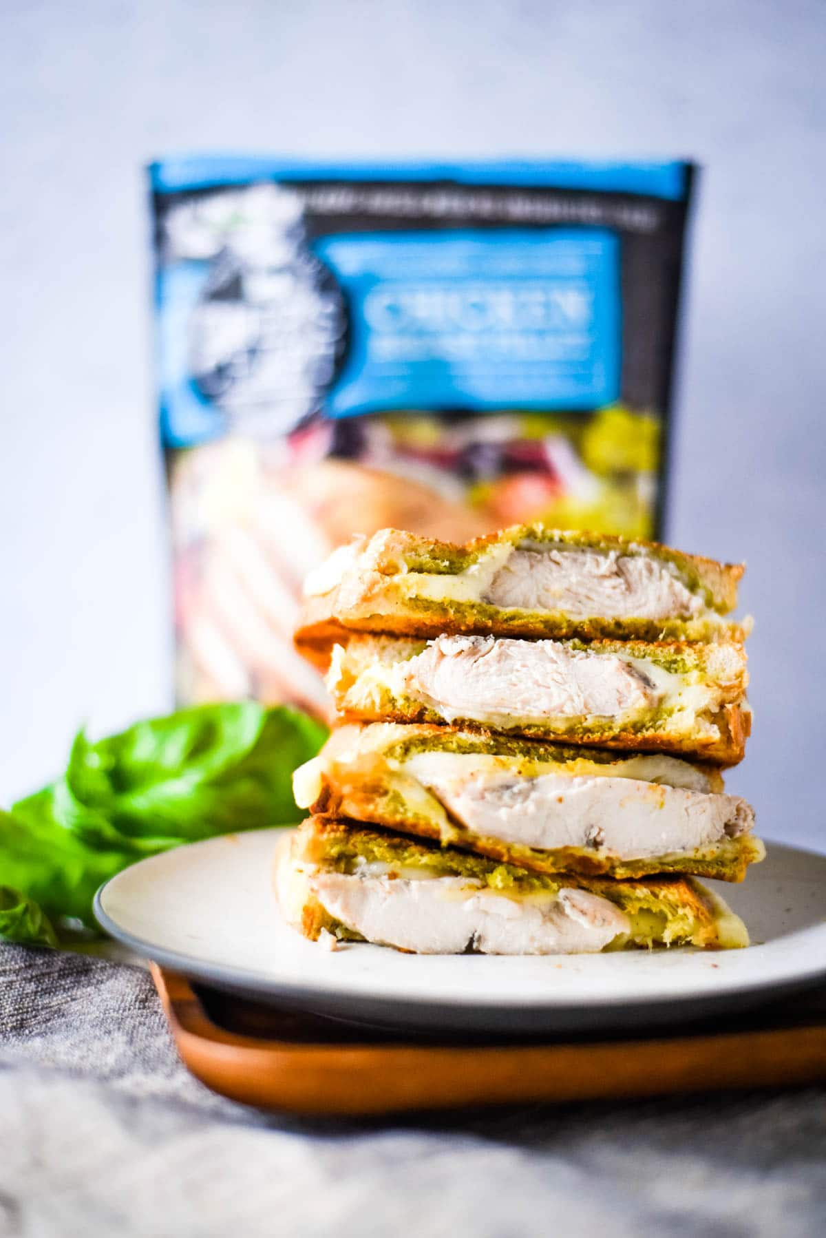 chicken grilled cheese stacked on plate with bag of chicken behind