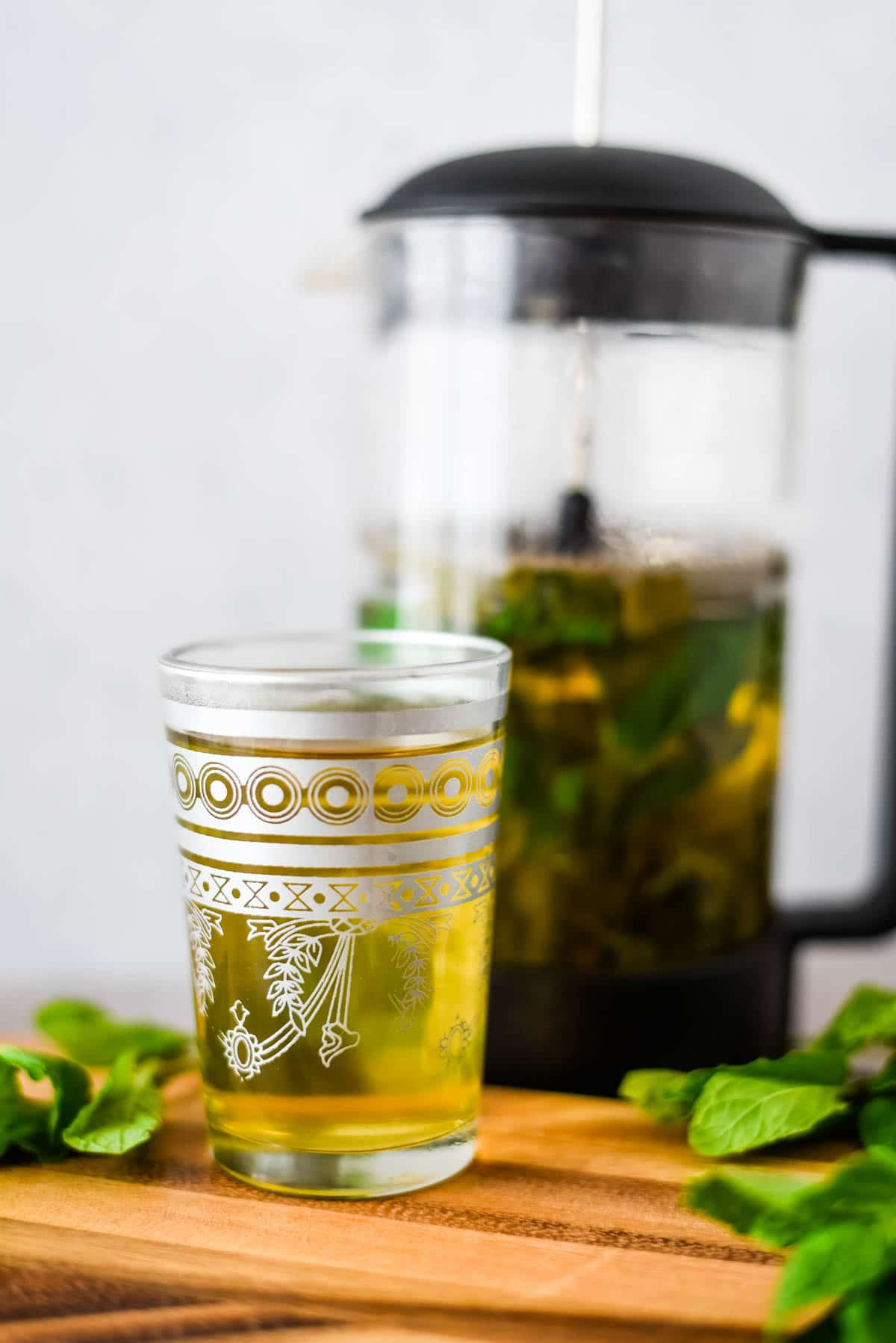 glass filled with green mint tea next to pitcher