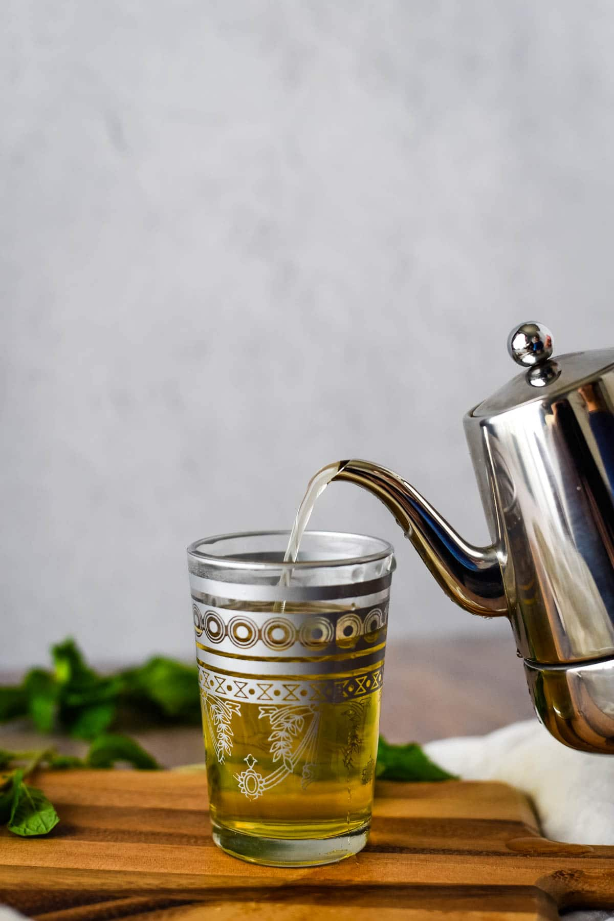 silver tea pot pouring into glass