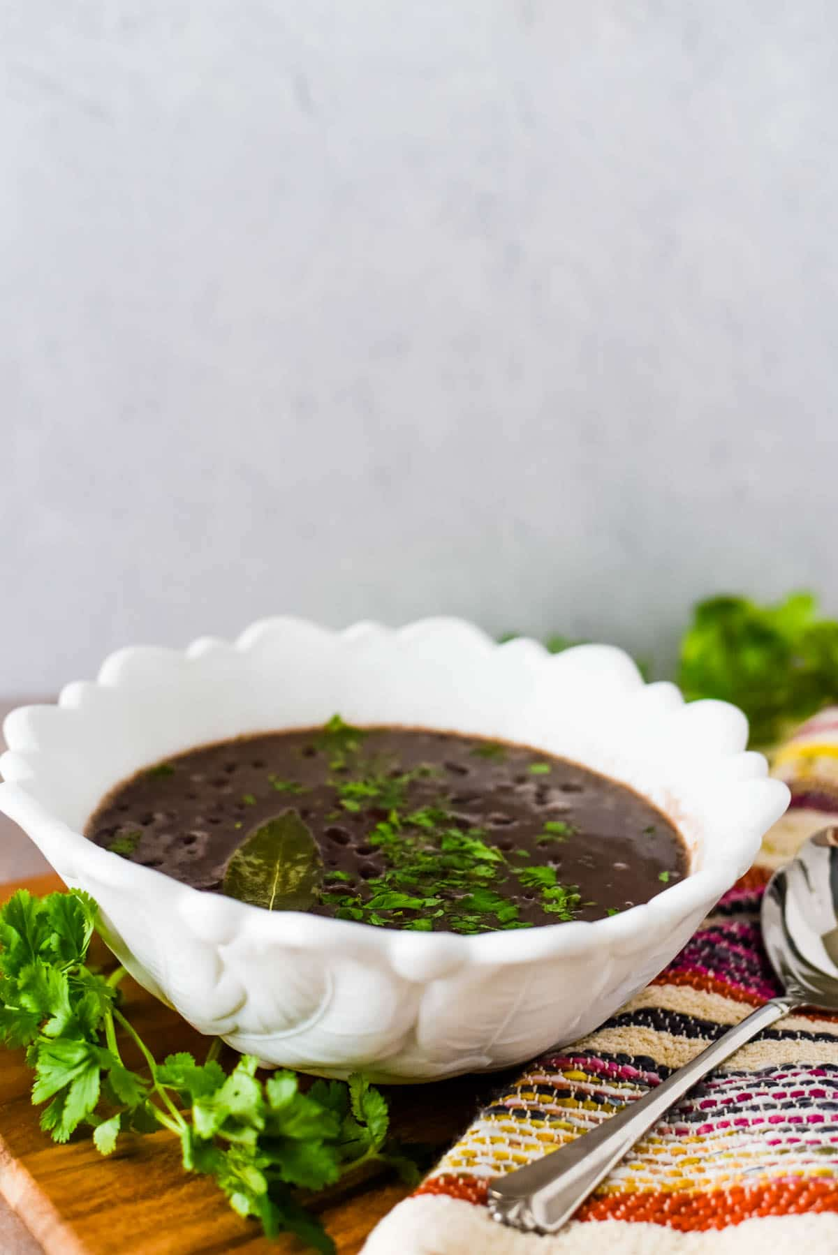 black beans in white serving bowl with cilantro beside