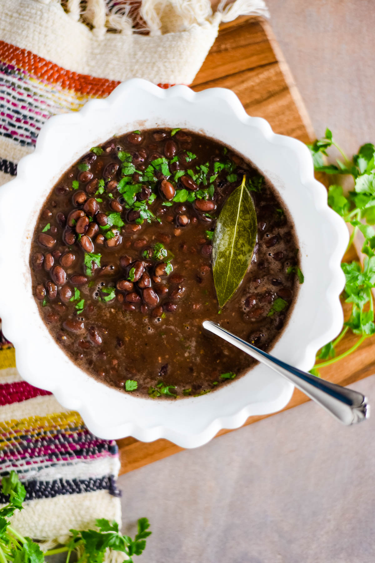 black beans in white bowl with spoon and cilantro