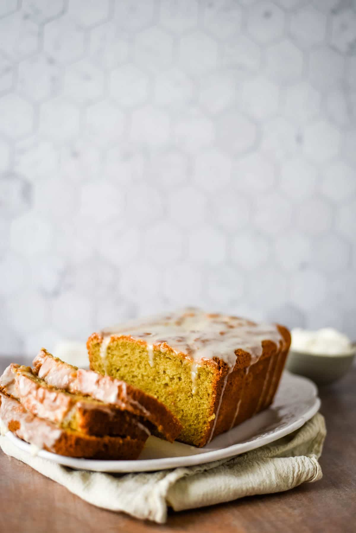 loaf of pound cake on tray with slices beside