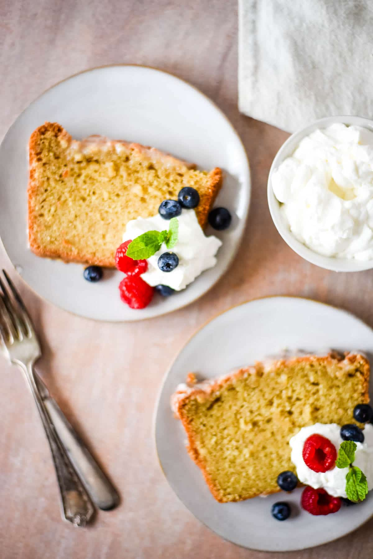 two slices of sourdough pound cake with whipped cream and berries