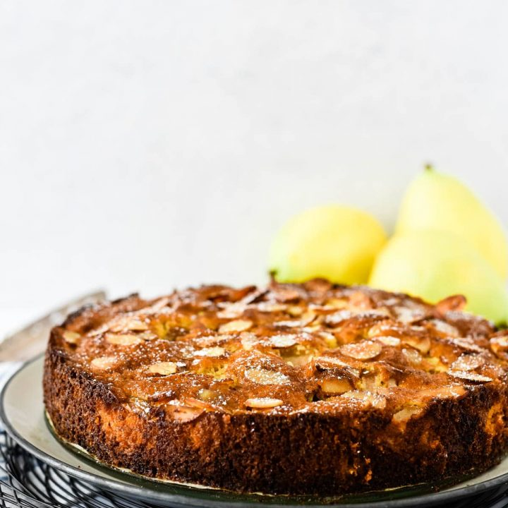 pear almond cake on platter with pears behind