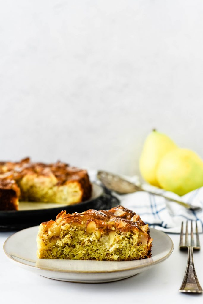 pear cake on place with serving platter and pears behind