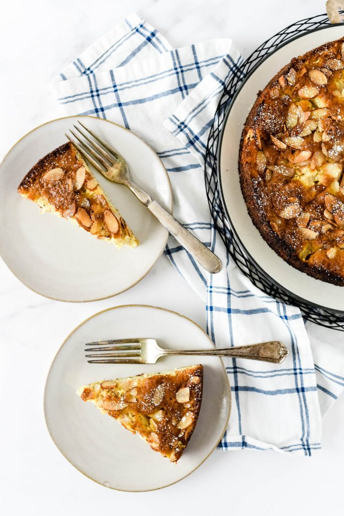 pear almond cake on platter with two plates and forks beside