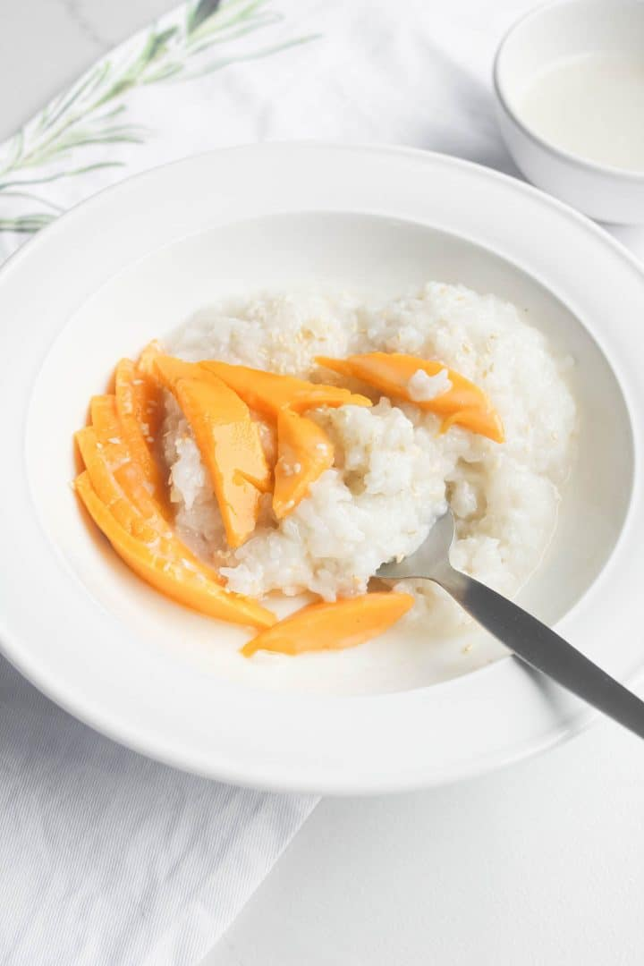 white bowl with spoon and rice and mango