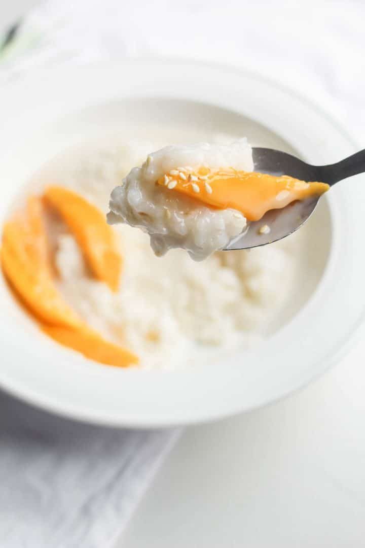 spoon with sweet sticky rice and mango