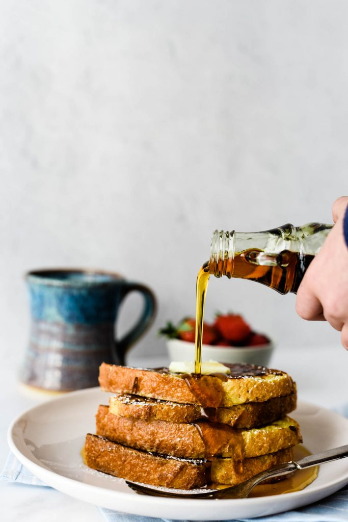 maple syrup being poured on stack of french toast