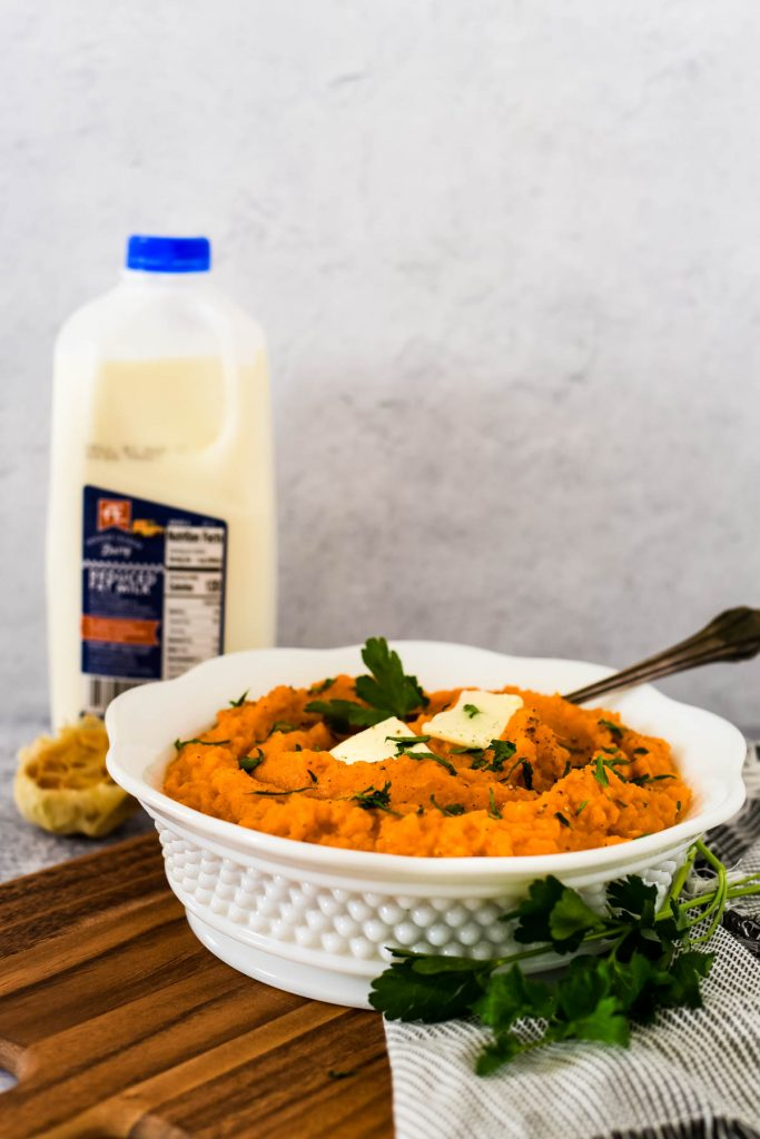 white bowl with mashed sweet potatoes, roasted garlic and ae dairy milk bottle