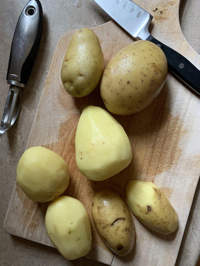 peeled potatoes on cutting board