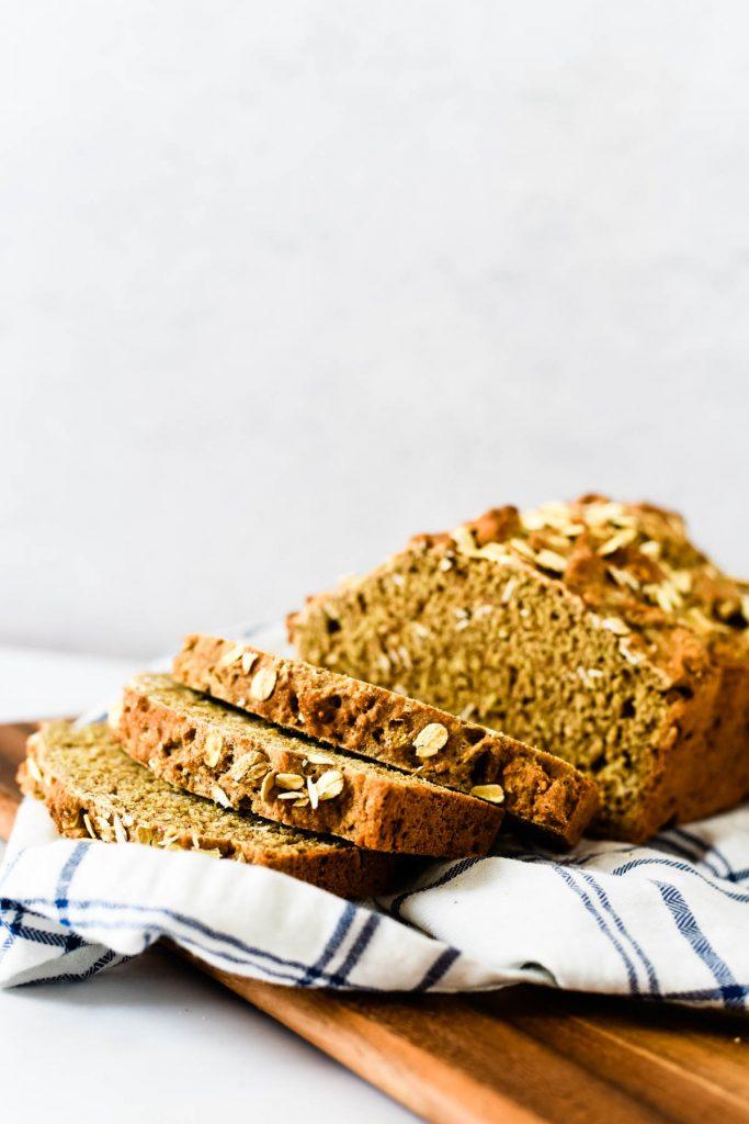 wheaten bread loaf with freshly cut slices beside it