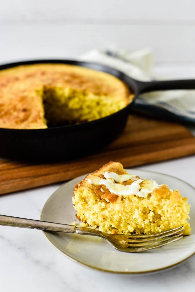 slice of cornbread on plate in front of cast iron skillet