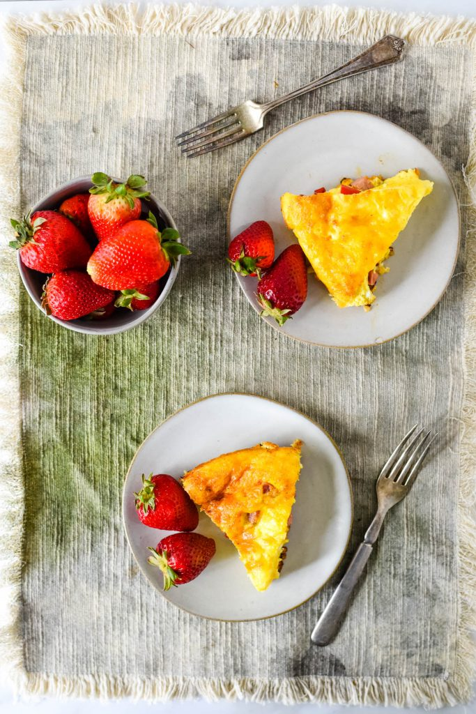 two slices of frittata on plates with bowl of strawberries