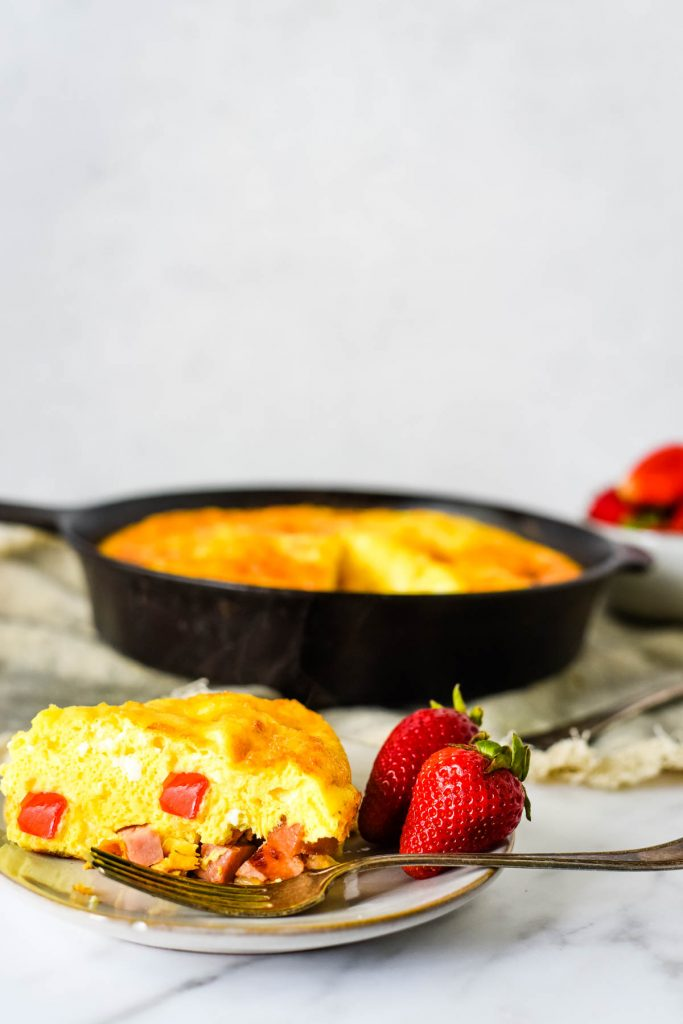 slice of frittata on small plate with cast iron skillet behind