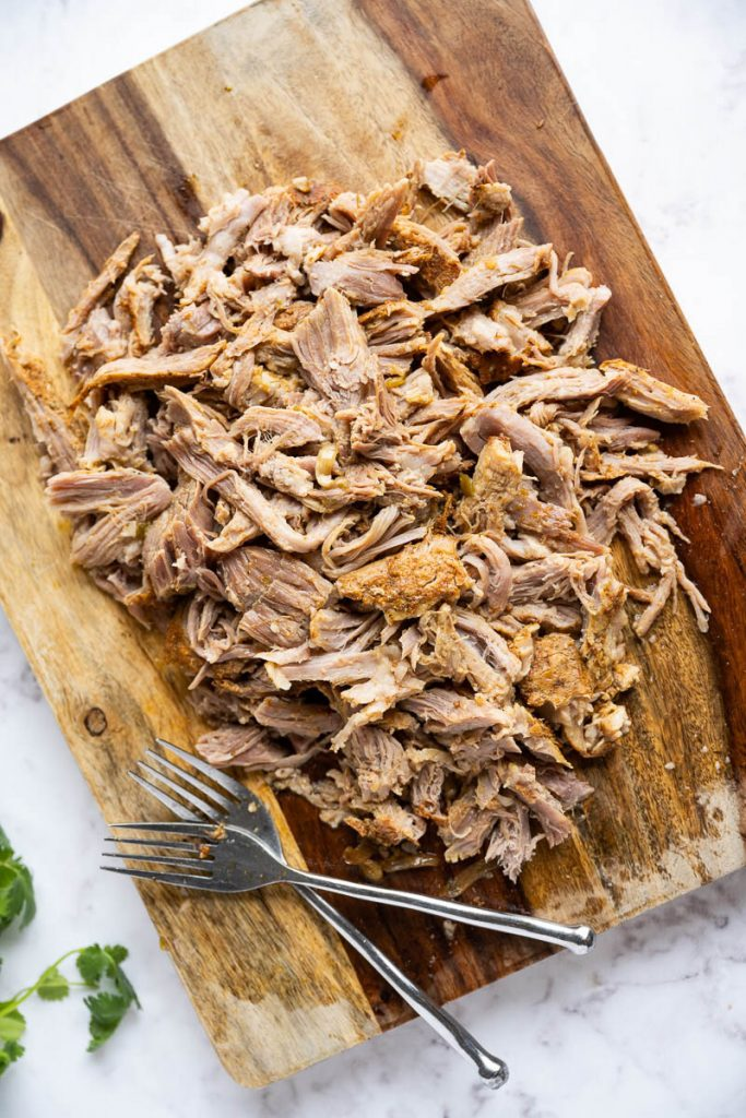 shredded pork roast on woden cutting board with to forks