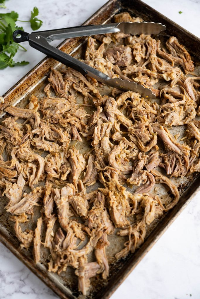slow cooker pulled pork carnitas on baking dish with tons