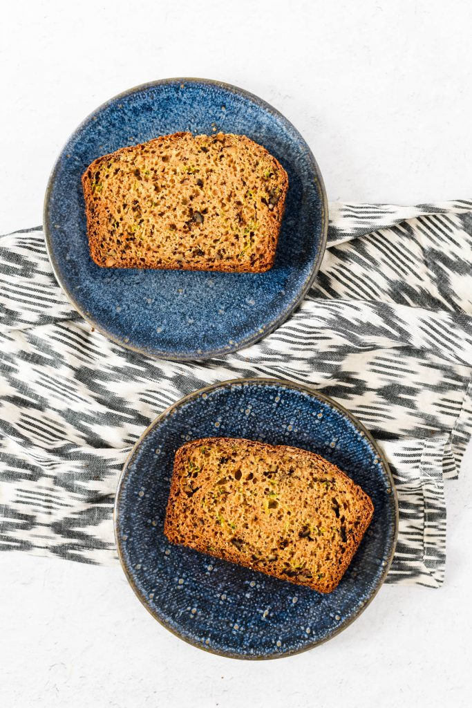 two slices of zucchini bread on blue plates
