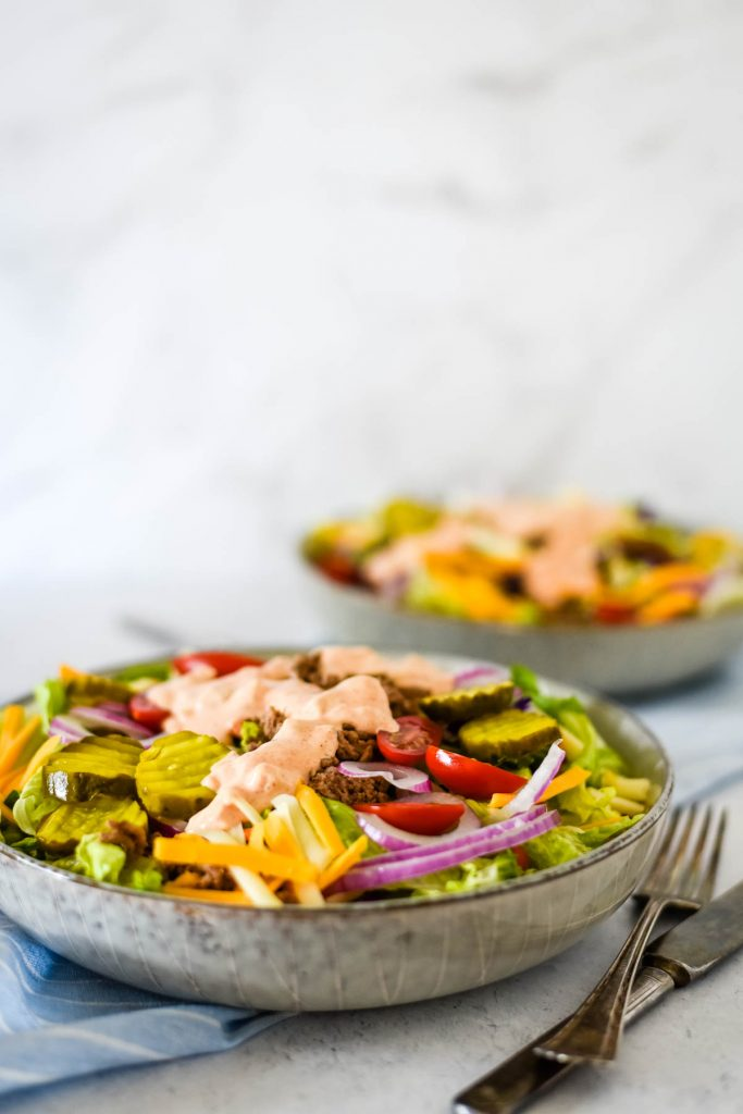 two plates of cheeseburger salad with cheese, dressing, and tomatoes