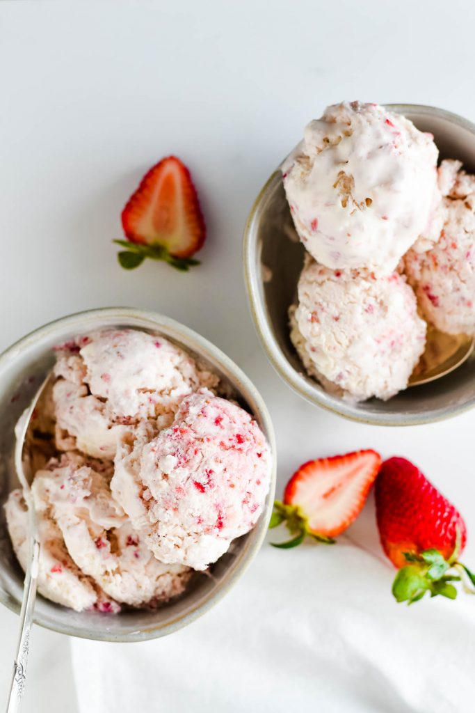 two bowls with scoops of strawberry ice cream and sliced strawberries beside