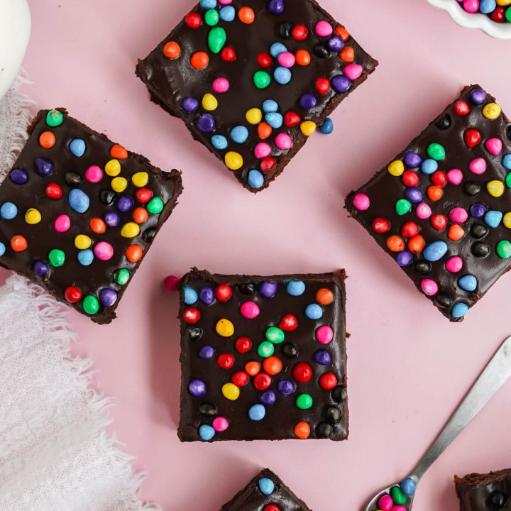 brownies with candy sprinkles on pink board