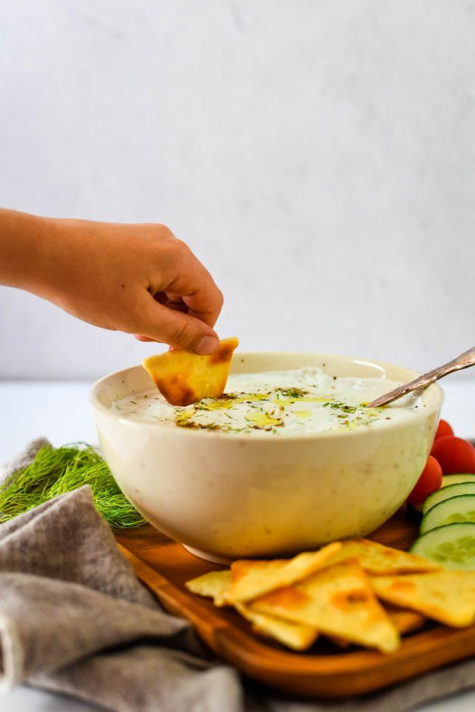 hand dipping pita chip into tzatziki sauce bowl