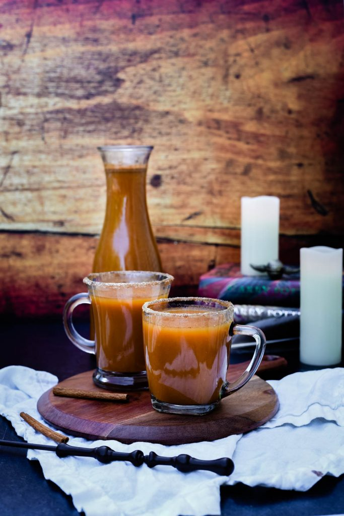 two glasses of pumpkin juice with candles and wand