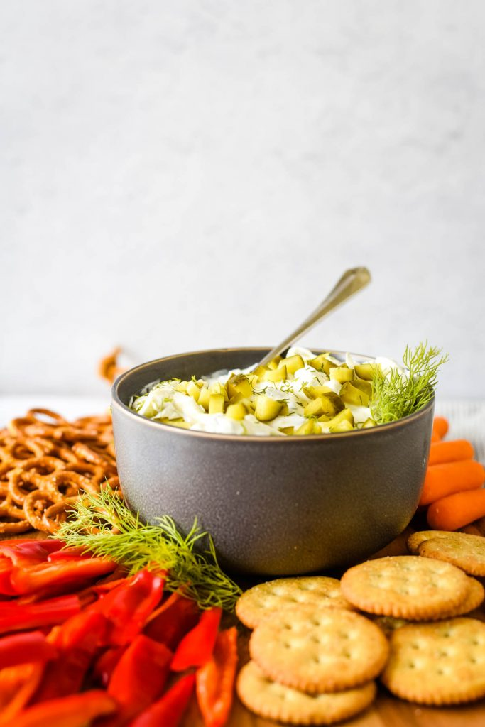 grey bowl with pickle dip surrounded by veggies