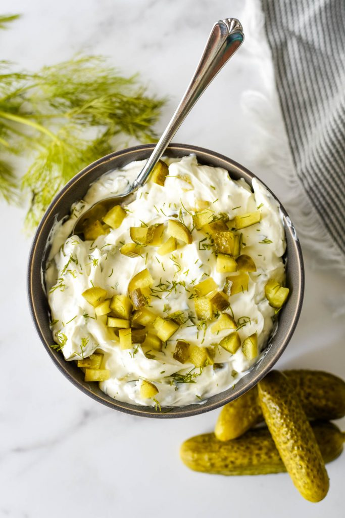 grey bowl with pickle dip, surrounded by dill and pickles